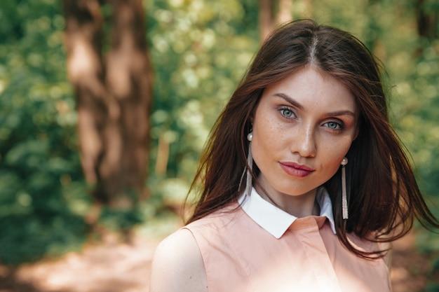 Lindo modelo feminino em pé de vestido rosa na floresta verde