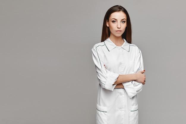 Lindo modelo feminino em uniforme médico posando em fundo cinza. jovem de casaco médico, copie o espaço para sua publicidade. conceito de saúde