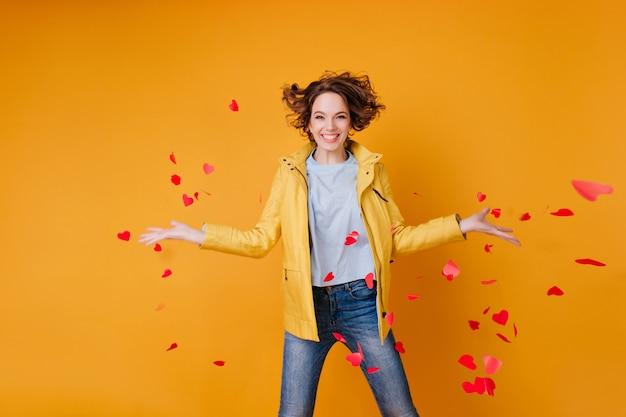 Lindo modelo feminino jogando fora os corações de papel e expressando felicidade. mulher encaracolada glamorosa comemorando o dia dos namorados.