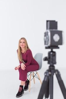 Lindo modelo feminino turva, sentado em uma cadeira no estúdio