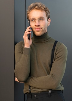 Lindo modelo masculino falando ao telefone ao ar livre