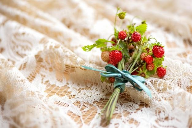 Lindo monte de galhos de morango silvestre com bagas vermelhas maduras na superfície têxtil