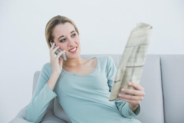 Lindo mulher sorridente telefonando com o smartphone sentado no sofá