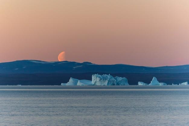 Lindo nascer da lua na groenlândia. iceberg no mar.