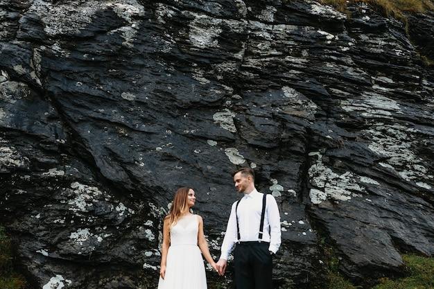 Lindo noivo e noiva de mãos dadas e olhando um para o outro sorrindo contra uma rocha negra nas montanhas.