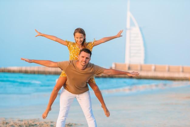 Lindo pai e filha na praia, aproveitando as férias de verão.