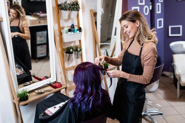 Lindo penteado de jovem adulta com cabelo roxo em cabeleireiro.