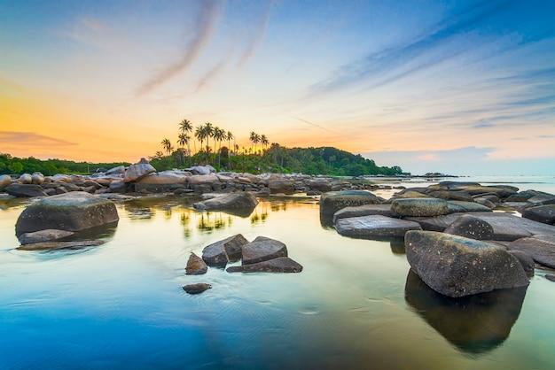 Lindo pôr do sol com fileiras de pedras e coqueiros na costa da indonésia de bintã