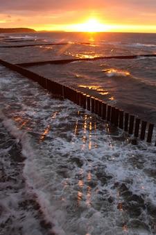 Lindo pôr do sol sobre o mar em clima de tempestade com reflexos vermelhos na água e na espuma do mar