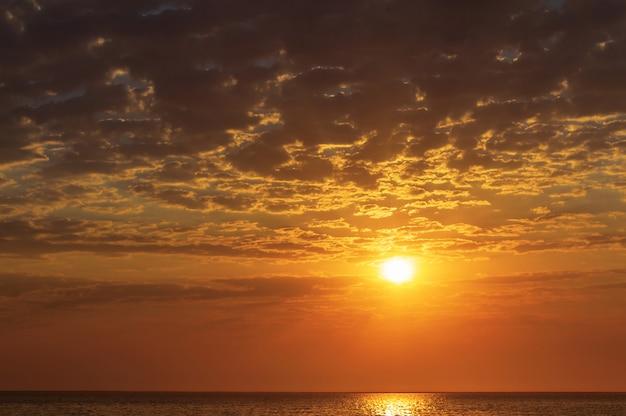 Lindo pôr do sol vermelho e sol forte no horizonte