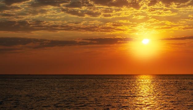 Lindo pôr do sol vermelho, nuvens escuras e oceano no horizonte