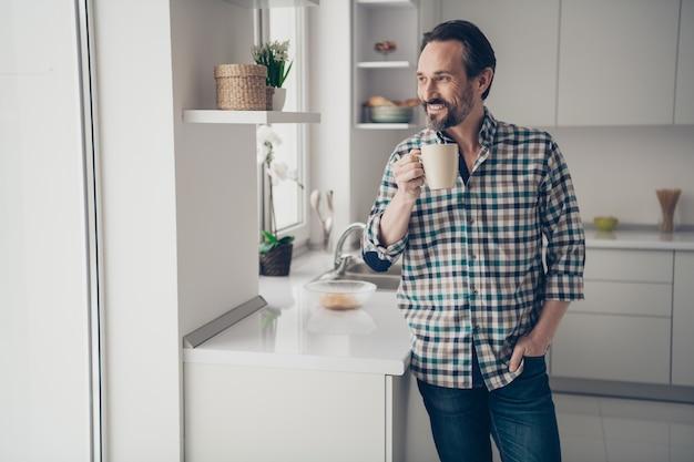 Lindo positivo otimista bom feliz cara segurando uma xícara de cacau fresco nas mãos, olhando pela janela para as folhas caindo na cozinha