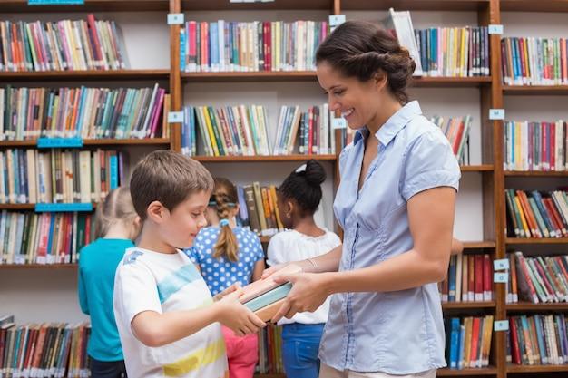 Lindo pupila e professor de livro de leitura na biblioteca