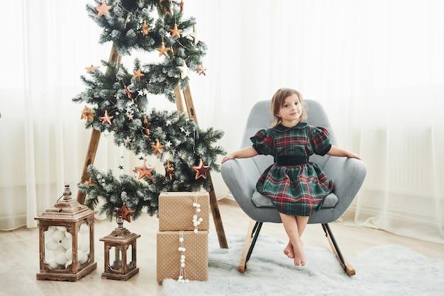 Lindo quarto branco. concepção de natal e feriados. menina bonitinha é senta-se na cadeira perto da escada decorada com estrelas e caixas de presente no chão