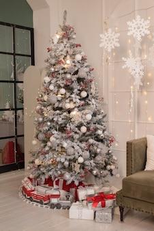 Lindo quarto decorado com uma árvore de natal e presentes embaixo.