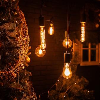 Lindo quarto escuro com lâmpadas antigas com luz amarela e uma árvore de natal com brinquedos dourados e guirlandas vintage