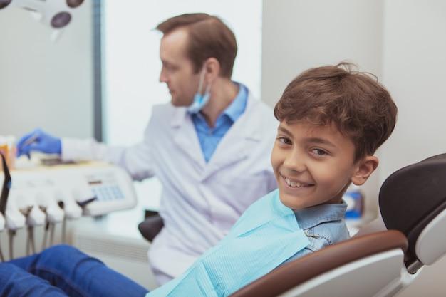 Lindo rapaz alegre, sorrindo, à espera de exame dentário por seu ortodontista