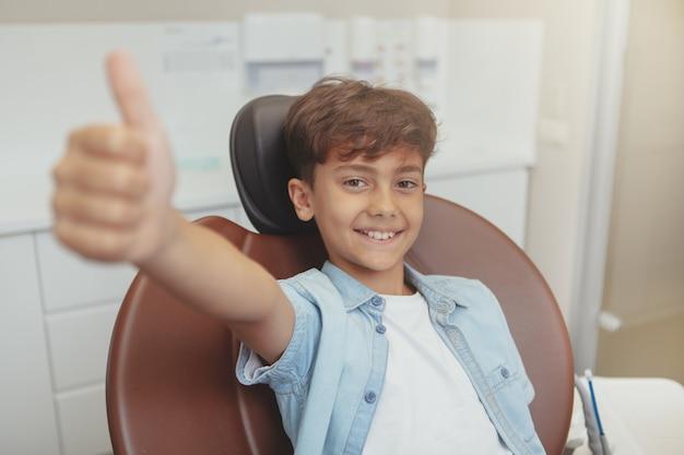 Lindo rapaz alegre sorrindo, mostrando os polegares para cima sentado em uma cadeira odontológica.