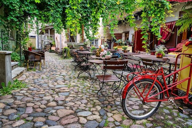 Lindo recanto com ambiente retrô com mesas, cadeiras e uma bicicleta velha.