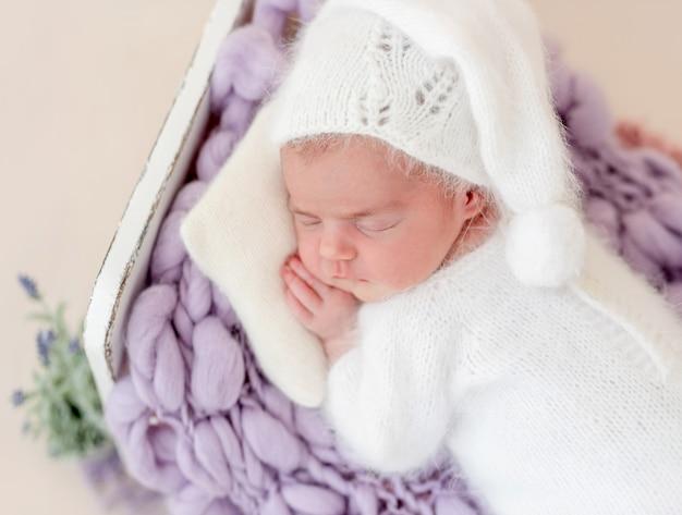Lindo recém-nascido dormindo na cama pequena