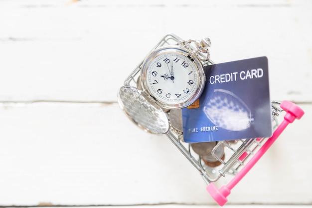 Lindo relógio de prata colar e moeda com cartões de crédito no carrinho de compras mini no chão de madeira branco