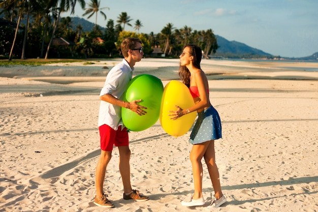 Lindo retrato de dois jovens felizes namorando e se divertindo na praia