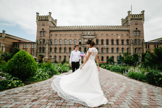 Lindo retrato noiva está dançando para o noivo e girando para trás perto da arquitetura restaurada antiga, prédio antigo, casa velha do lado de fora, palácio vintage ao ar livre.