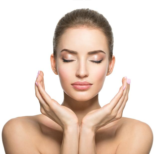Lindo rosto de jovem mulher branca com pele saudável - isolada no branco. conceito de cuidados com a pele. modelo feminino toca o rosto.