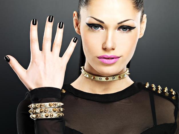 Lindo rosto de moda mulher com unhas pretas e maquiagem brilhante. garota sexy e elegante com pulseira de espinhos no pescoço