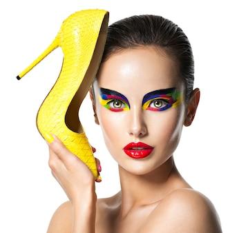 Lindo rosto de mulher com uma maquiagem vívida de olhos segura o salto alto amarelo. conceito de moda.