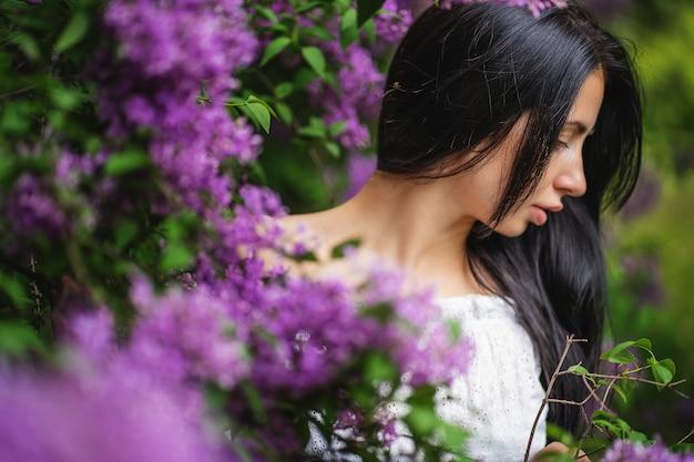 Lindo rosto de mulher em perfil. lilás florescendo