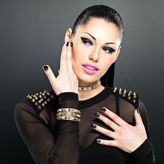 Lindo rosto de mulher fashion com unhas pretas e maquiagem brilhante. garota sexy e elegante com pulseira de espinhos no pescoço