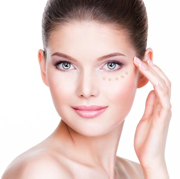 Lindo rosto de mulher jovem com base cosmética em uma parede branca de pele. conceito de tratamento de beleza.