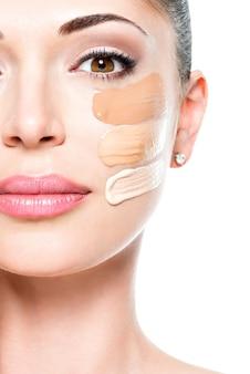 Lindo rosto de mulher jovem com base cosmética sobre a pele.