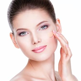 Lindo rosto de mulher jovem com base cosmética sobre uma pele sobre fundo branco. conceito de tratamento de beleza.