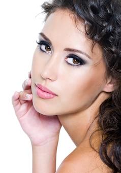 Lindo rosto de mulher jovem com pele limpa. menina com cabelos muito cacheados. maquilhagem de olhos brilhante