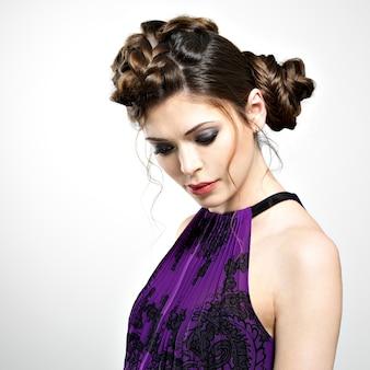 Lindo rosto de mulher jovem com penteado elegante com design de tranças e maquiagem fashion