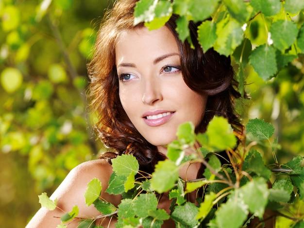 Lindo rosto de uma jovem mulher sexy posando perto de uma árvore verde na natureza