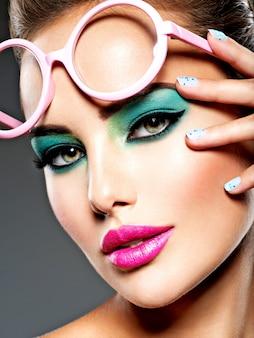 Lindo rosto de uma mulher com maquiagem vívida verde de olhos e óculos cor de rosa.
