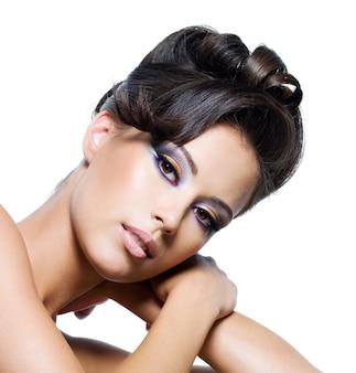 Lindo rosto de uma mulher glamourosa com penteado encaracolado moderno e maquiagem multicolorida