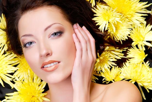 Lindo rosto feminino com camomilas amarelas na cabeça