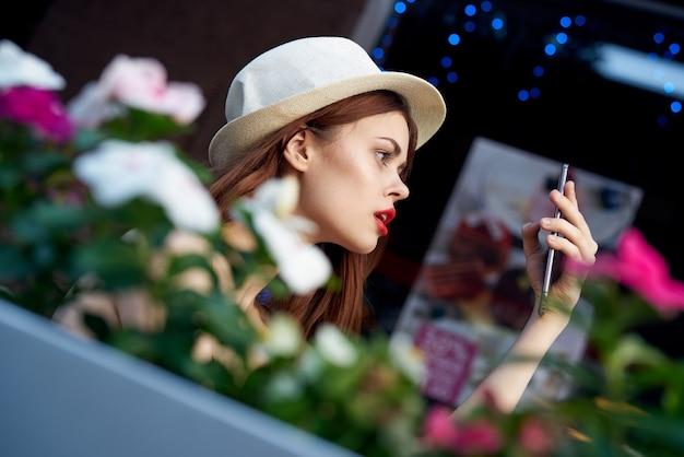 Lindo rosto feminino com chapéu de maquiagem brilhante e modelo de flores de verão em um café na natureza