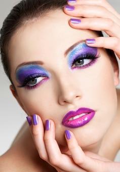 Lindo rosto feminino com maquiagem fashion de olhos e manicure roxa de beleza. ela colocou as mãos no rosto.