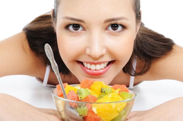 Lindo rosto feminino jovem debaixo da tigela com salada de frutas
