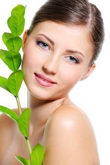 Lindo rosto feminino sorridente com uma pele limpa e saudável e uma planta perto do corpo