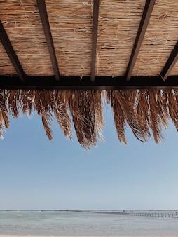 Lindo salão com cobertura para relaxar na praia com barraca feita de folhas de palmeira seca e vista para o mar