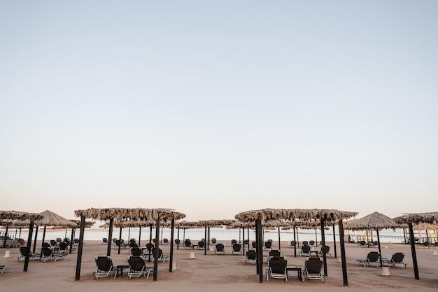 Lindo salão com cobertura para relaxar na praia com vista lateral da areia e do mar e céu azul