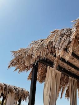 Lindo salão com cobertura para relaxar na praia com vista lateral para o mar e céu azul
