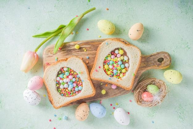 Lindo sanduíche de café da manhã doce idéia criativa para lanche de páscoa ou almoço. sanduíche de torrada com pasta de amendoim e macarrão de chocolate, com granulado colorido de açúcar, vista superior.