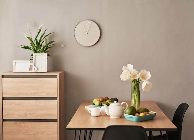 Lindo serviço de chá na mesa de madeira. decoração de interiores para casa, buquê de flores em um vaso, mesa com conjunto de bule de chá.